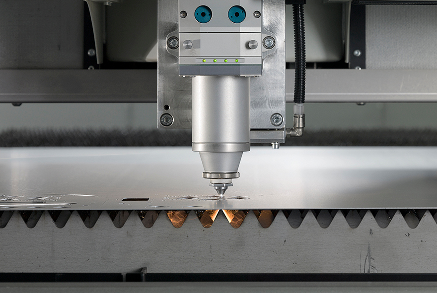 Laser cutting head of a sheet and tube laser cutting system